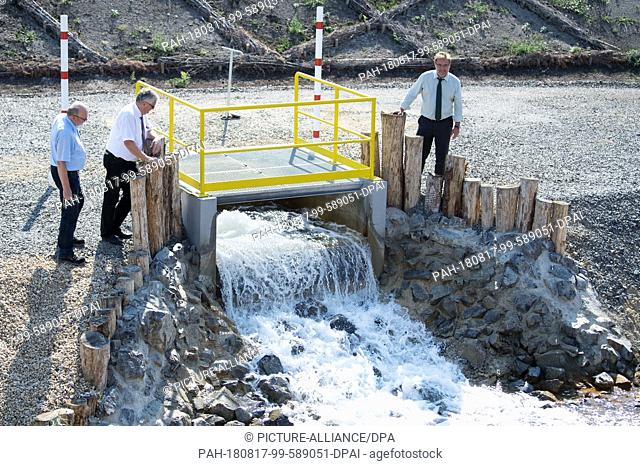 17 August 2018, Gemrany, Weisswasser: Representatives of Lausitz Energie Bergbau AG (LEAG) are standing at an inlet trench at a press event on the occasion of...