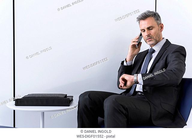 Businessman talking on the phone and checking the time