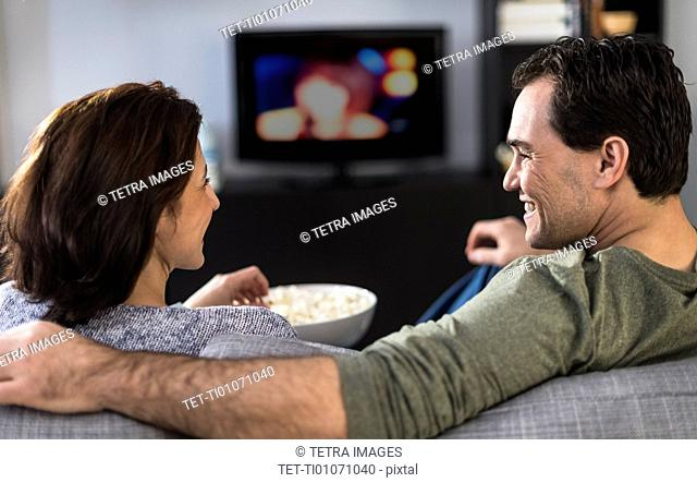 Rear view of couple watching tv