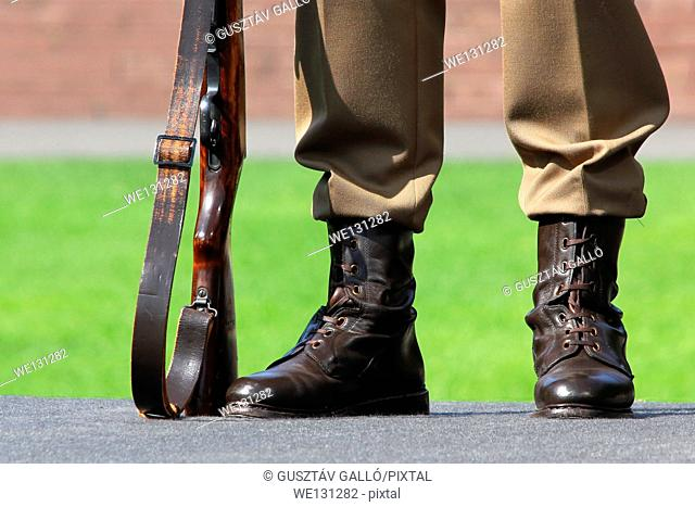 A soldier stands next to his feet and rifle on guard