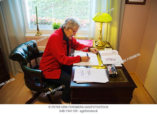 Woman in her early 70s doing paperwork Finland Europe