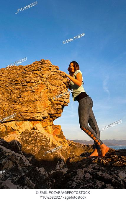 Young woman is watching sunset besides big rock