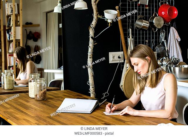 Woman sitting at table in her kitchen writing down something