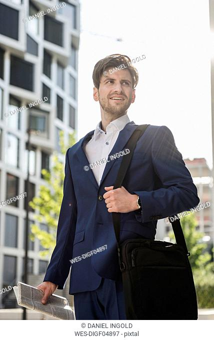 Smiling businessman with laptop bag and newspaper in the city looking around
