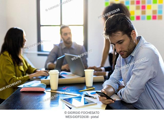 Businessman checking cell phone during a meeting in office