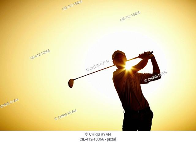 Silhouette of man swinging golf club