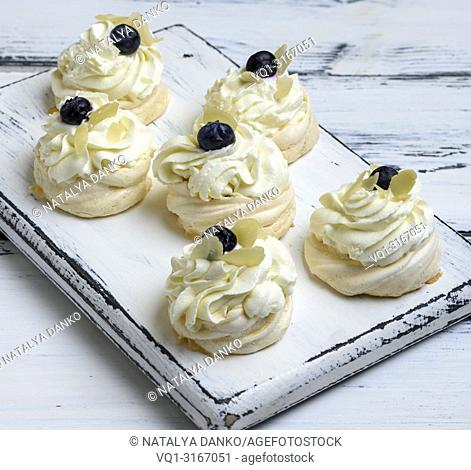 baked round meringues with whipped cream on a white wooden board, close up