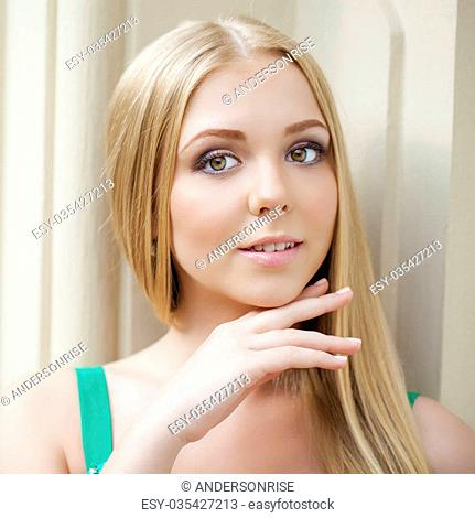 Close up portrait of a beautiful young blonde woman, indoor