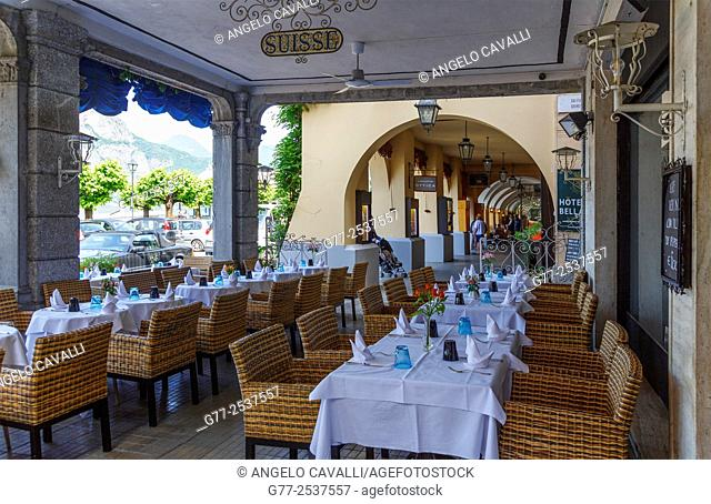 Set up tables in a restaurant under the arcades facing the lake in Bellagio, Lake of Como, Italy