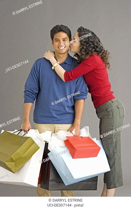 Woman kissing boyfriend holding shopping bags