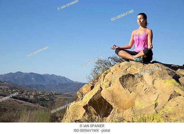 Mature woman practicing yoga lotus pose on hill, Thousand Oaks, California, USA