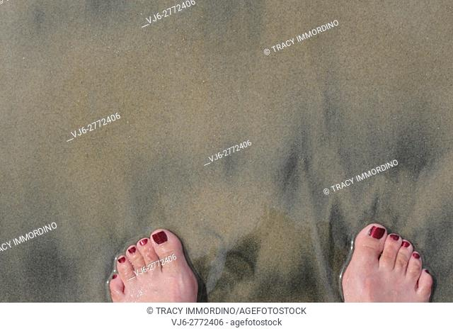 Close up of two feet with painted toenails in the tan and black sand at Torrey Pines Natural Reserve in San Diego, California, USA