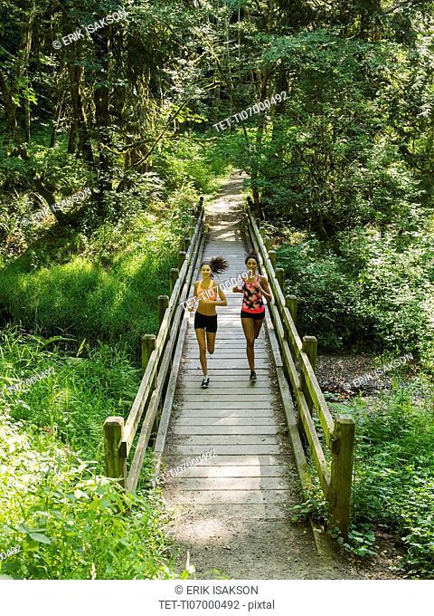 Two young women running over wooden footbridge