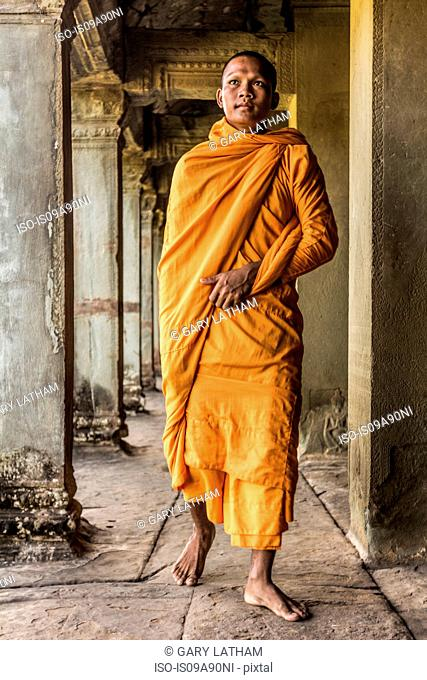 Young Buddhist monk walking through temple, Angkor Wat, Siem Reap, Cambodia