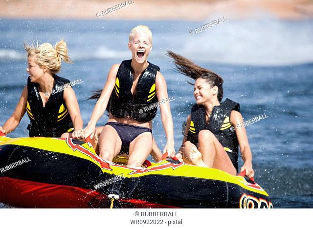 Four women on inner tube wearing life jackets