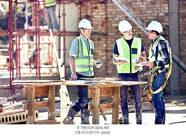 Construction workers and foreman talking at sunny construction site