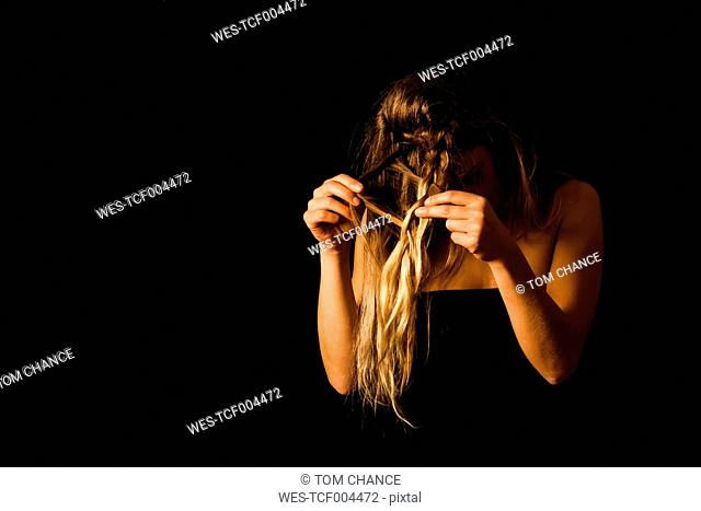 Woman disentangling her hair in front of black background