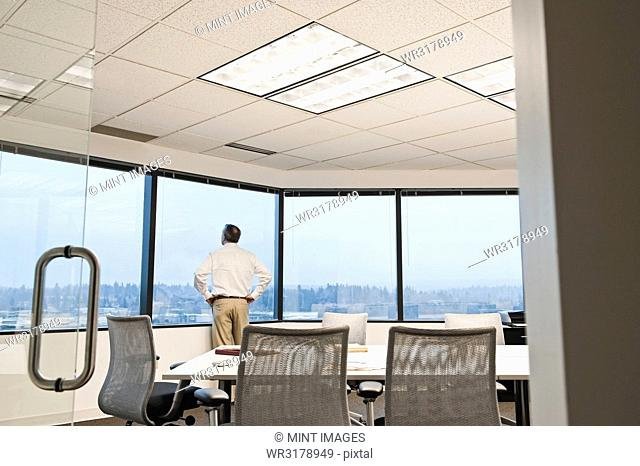 Businessman standing at a window before the next meeting in a conference room