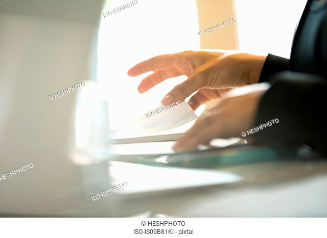 Hands of businesswoman organising paperwork at office desk