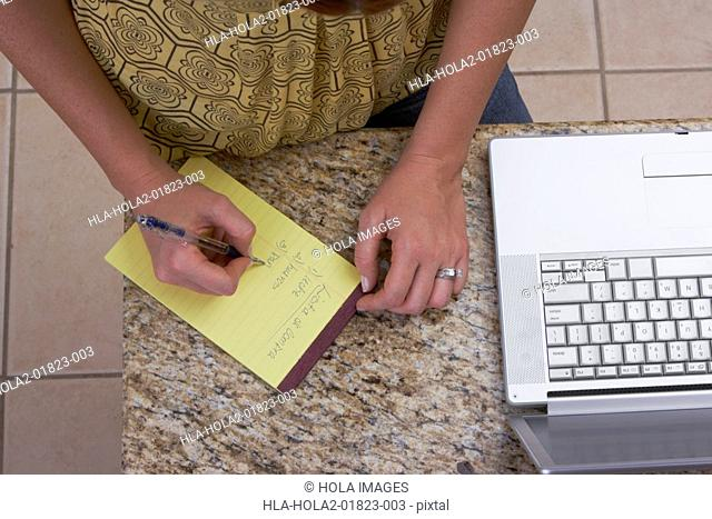 Mid section view of a woman writing on a notepad