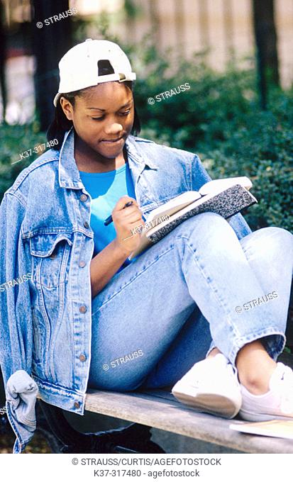 Teenage african american schoolgirl writing in notebook