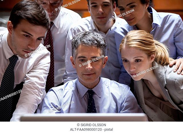 Business associates crowd around colleague looking over his shoulder at laptop computer