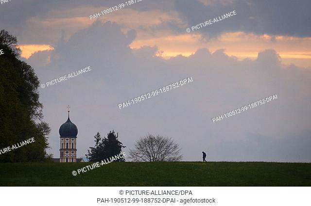 12 May 2019, Bavaria, Marktoberdorf: A walker walks under thinning clouds in front of the tower of the parish church Sankt Martin