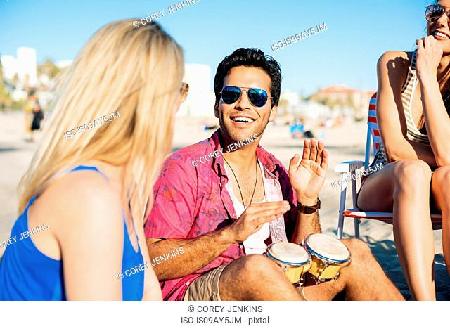 Young man with friends bongo drumming on beach, Santa Monica, California, USA