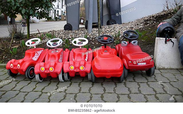 bobby cars standing side by side on a pavement, break, Germany