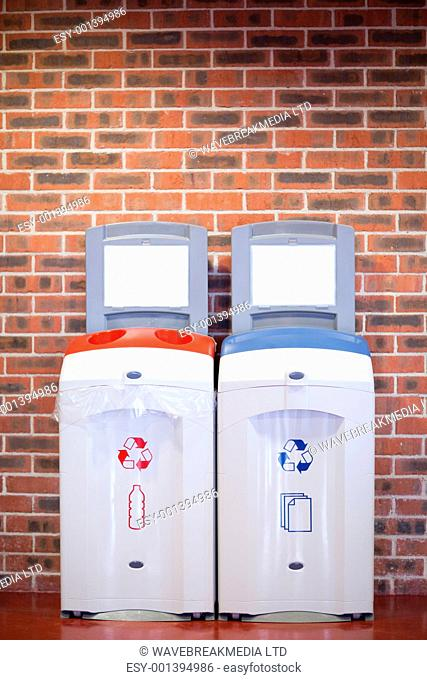 Portrait of recycling bins against a wall