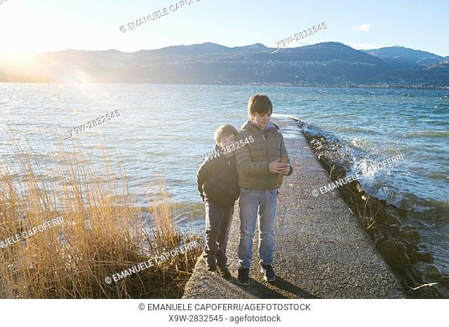 brothers children on the pier in the beach of Lake Maggiore