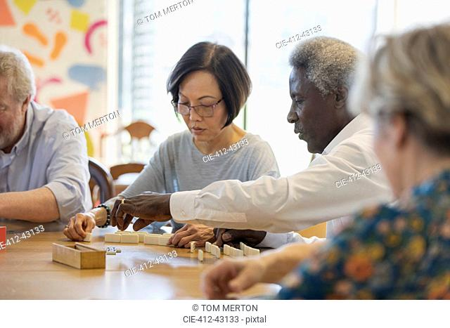 Senior friends playing mahjong at table in community center