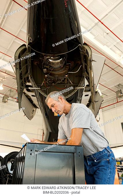 Caucasian man working in airplane hangar