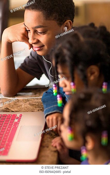 Close up of teenage boy and sisters at dining table using laptop