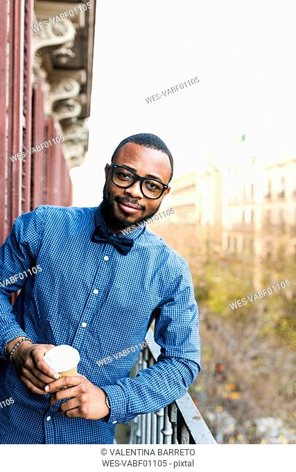 Portrait of smiling young man on balcony with takeaway coffee