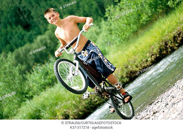 Young teenage youth wearing swimming trunks, balancing on back wheel of his mountain bike