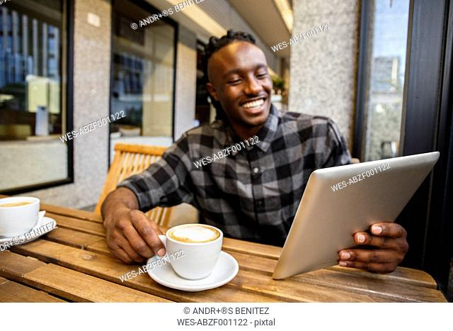 Young man sitting in cafe, using digital tablet
