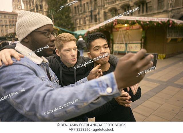 young men taking selfie in front of Neues Rathaus and Christmas market at Marienplatz in Munich, Germany