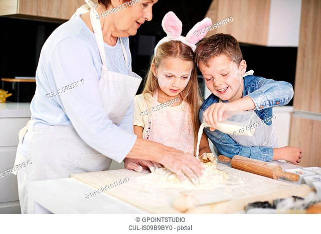 Girl and brother helping grandmother easter bake at kitchen counter