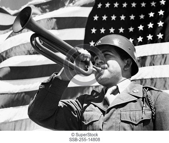 Army soldier blowing a bugle in front of an American flag