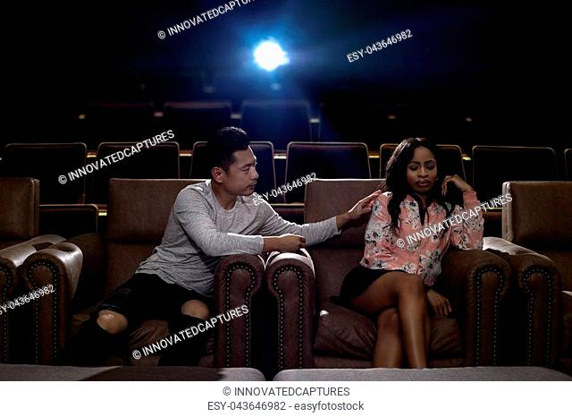 Young interracial dating couple in a movie theater watching a show. The man is asian and the woman is black. They are fighting and about to break up