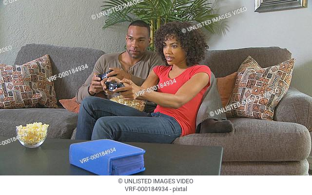Couple playing video games on couch