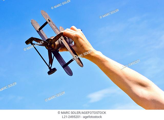 Close-up of hand holding a model airplane against blue sky