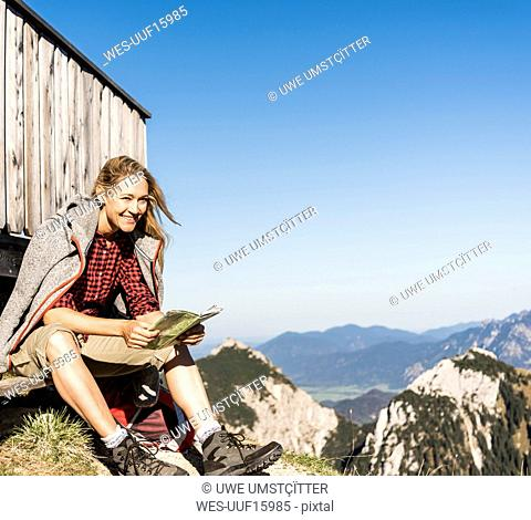 Laughing woman taking a break at a mountain hut, holding map