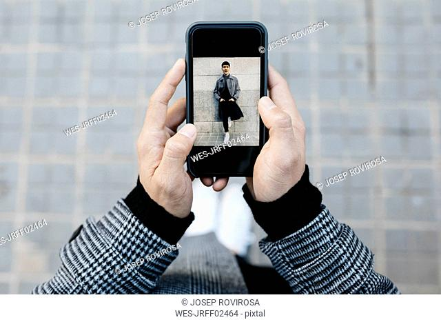 Man holding smartphone with photo of himself, close-up