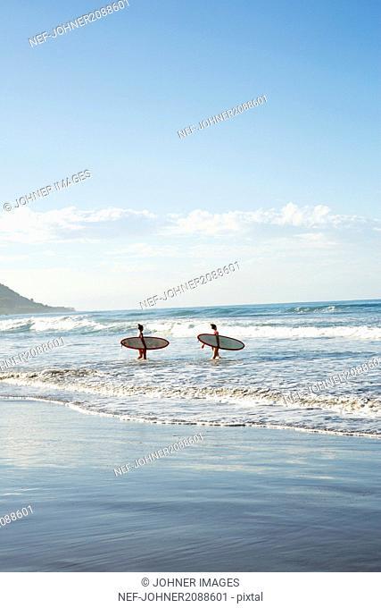 Teenage girls walking with surfboards in sea