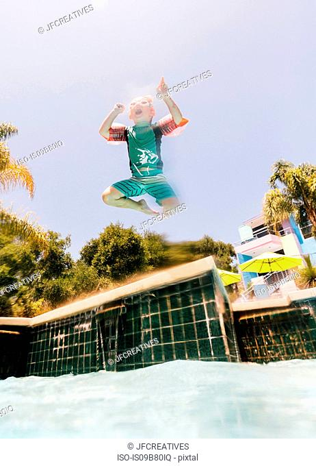 Young boy jumping into outdoor swimming pool, low angle view