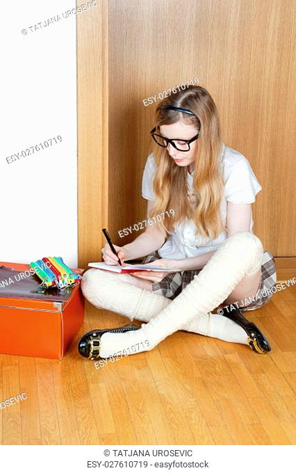 Young female pupil seating on floor and doing her homework