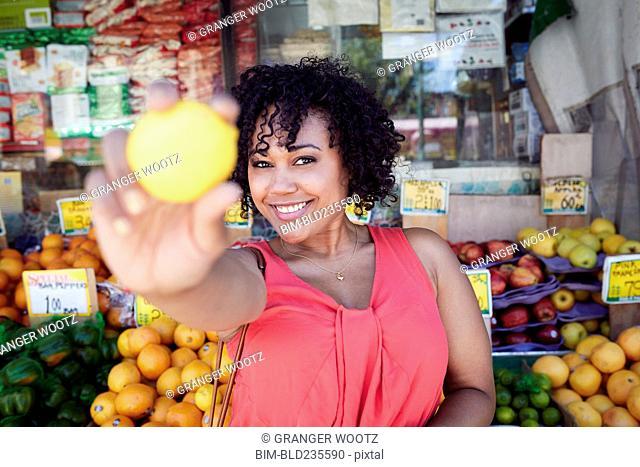 Smiling woman showing lemon at fruit stand