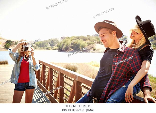 Caucasian woman taking picture of couple in park